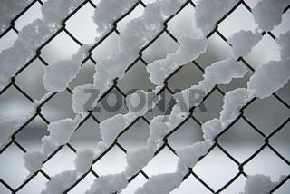 Maschendrahtzaun mit Rauhreif, Schnee und Eis