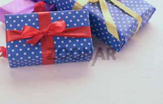 boxes packed in festive blue paper and tied with silk ribbon on white background, birthday gift, surprise