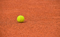 Yellow tennis ball on red clay ground court