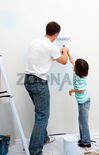 Caring father teaching his son how to paint
