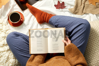 young woman reading book at home in autumn