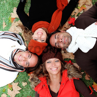 group of happy smiling young adults in autumn