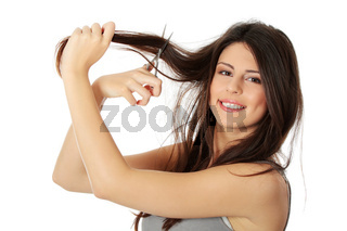 Beautiful young woman is holding scissors.
