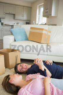 Happy couple lying on floor with moving boxes