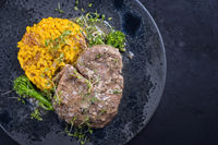 Modern style traditional braised Italian ossobuco alla Milanese with saffron risotto and baby broccoli in white wine meat sauce served as top view on a Nordic design plate with copy space right