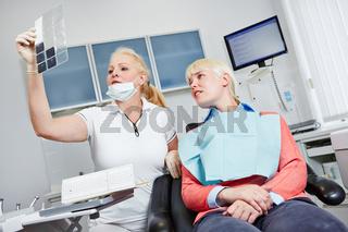 Zahnarzt betrachtet Röntgenbild eines Patienten