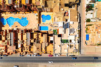 Directly above aerial view residential typical houses with swimming pool and town road with cars. Province of Alicante