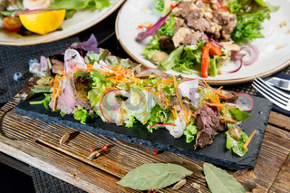 Meat appetizer made from pieces of veal, sauce and vegetables. Green salad to decorate the dish. Close-up. Concept - ingredients for serving