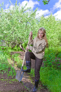 The young woman digs up a garden-bed with the first sprouts on a summer cottage