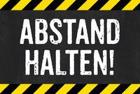 Sign with caution stripes - Keep distance in german - Abstand halten