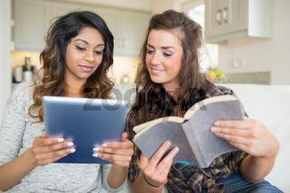 Two girls reading a book and holding a tablet computer