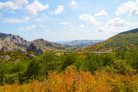 Autumn mountain landscape - yellow and red trees against blue mountains and blue sky with white clouds on a sunny day