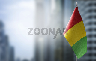 A small flag of Guinea on the background of a blurred background