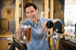 Bar tender offering glass of beer to customer