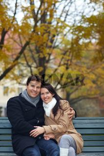 Mann umarmt Frau auf Parkbank