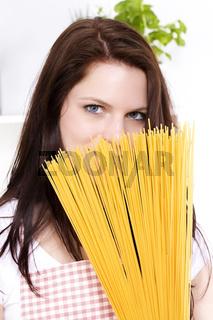 junge frau versteckt sich hinter spaghetti