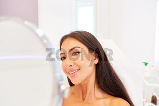 Glückliche Frau schaut auf ihr Gesicht im Spiegel