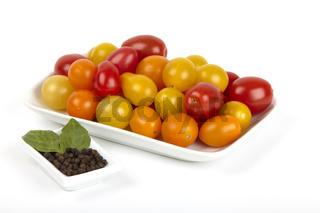 Schale mit fischen Bio Tomaten und Pfefferkörnern.