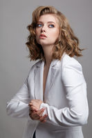 Portrait of young dark blonde woman in casual white jacket on gray background.