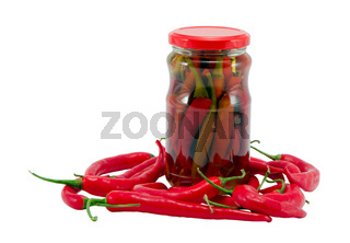 Red hot chilli pepper paprika preserved in glass pot surrounded by natural ones. Healhy ecologic food. Resource for winter time.
