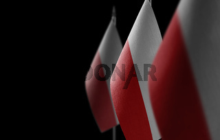 Small national flags of the Poland on a black background