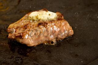 Stück Rindfleisch mit Kräuterbutter auf einem Raclette Grill