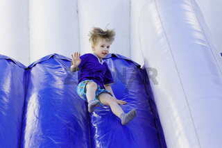 Boy slides down an inflatable slide