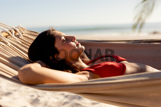Young caucasian woman laying on hammock on beach