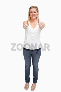 Joyful blonde woman placing her thumbs up