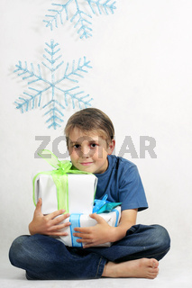 Smiling boy holding Christmas Presents