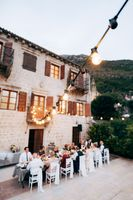 A long glowing garland of incandescent bulbs against the facade of the old villa. Guests sit at a table at a wedding banquet during a wedding dinner.