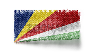 Seychelles flag on a piece of cloth on a white background