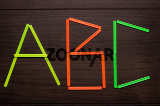 abc formed with counting sticks over wooden background