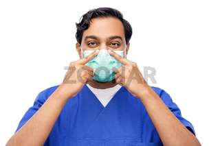 indian male doctor in blue uniform putting mask on