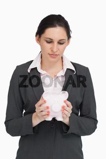 Brunette businesswoman holding a piggy-bank