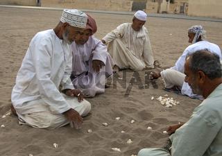 omanische Männer spielen Hawalis mit Muscheln
