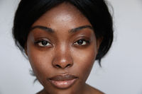 Close-up portrait of young black woman with natural skin, posing in the studio.