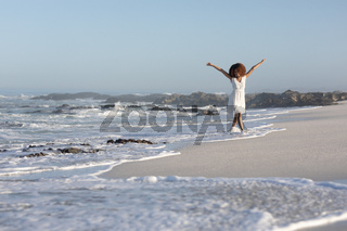 A mixed race woman with her arms outstretched on beach on a sunny day
