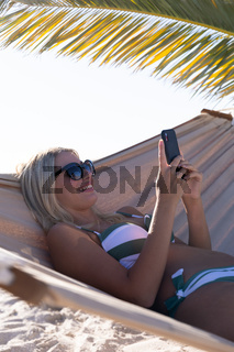 Caucasian woman lying on a hammock and using a smartphone at the beach.