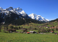 Village Gsteig bei Gstaad and snow covered mountains on a spring day.
