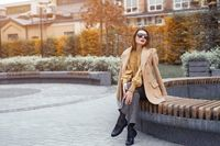 A beautiful girl in an autumn coat and beige sunglasses sits on a bench waiting for her date or girlfriends. Toned photo