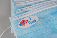 I Voted paper sticker on medical face mask to illustrate in person voting