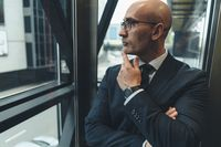 Thoughtful businessman in suit in eye glasses looking away in the window or glass elevator with a busy street view. Focused business man face looking outside of the window