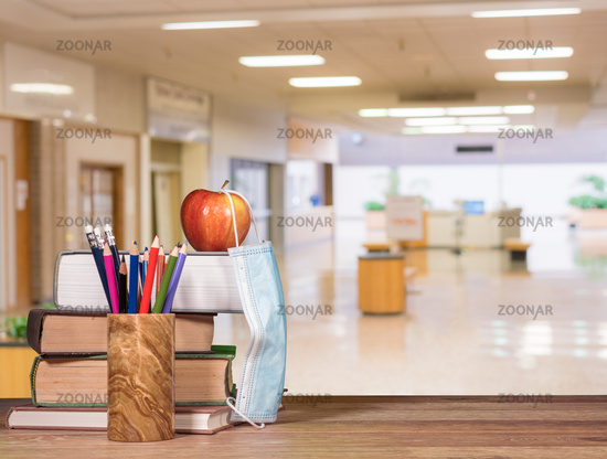Back to school background concept with stack of books, pencil, apple with face mask