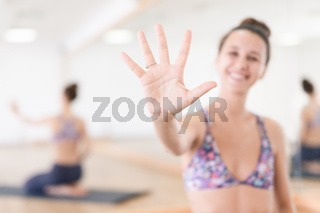 Fit sporty active woman smiling, wearing fashion sportswear showing an open palm to the camera in yoga studio. Active urban lifestyle.
