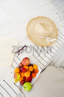 Plate of fruit assortment and book on bed
