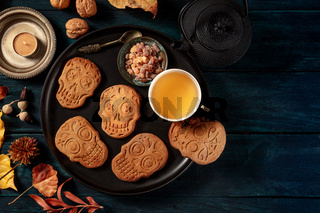 Halloween ginger cookies in the shape of skulls, homemade Dia de los muertos biscuits, shot from the top with a place for text