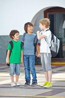 Drei Kinder reden auf Schulhof miteinander