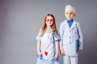 Cute boy and girl in medical uniform playing like doctors.