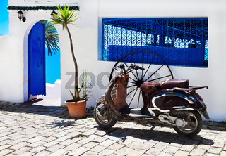 Vintage image of red scooter on the street Sidi Bou Said town